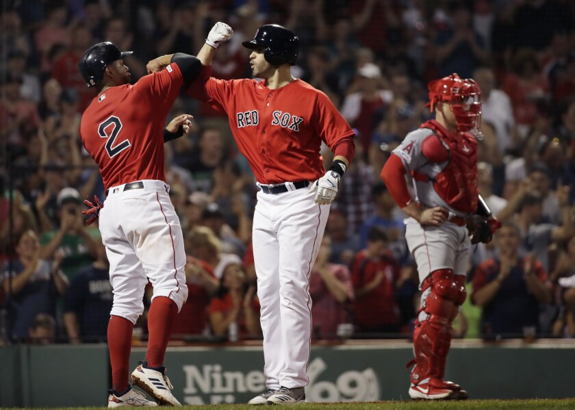 Boston Red Sox's J.D. Martinez, right, celebrates his two-run home run with Xander Bogaerts, next to Angels catcher Max Stassi during the fourth inning on Friday in Boston.