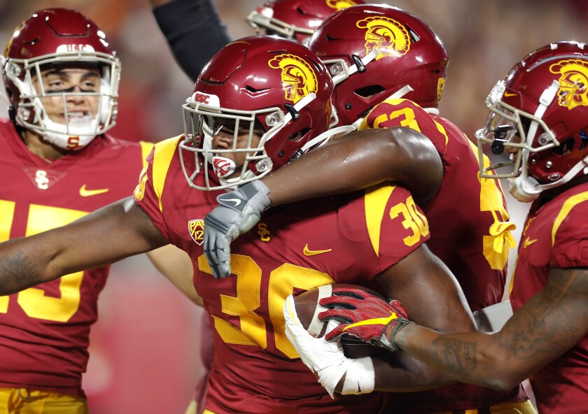 USC tailback Markese Stepp is swarmed by teammates after scoring a touchdown against Utah in the fourth quarter at the Coliseum on Friday.