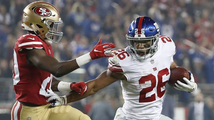 New York Giants running back Saquon Barkley tries to get past San Francisco's Jimmie Ward on Nov. 12 at Levi's Stadium.