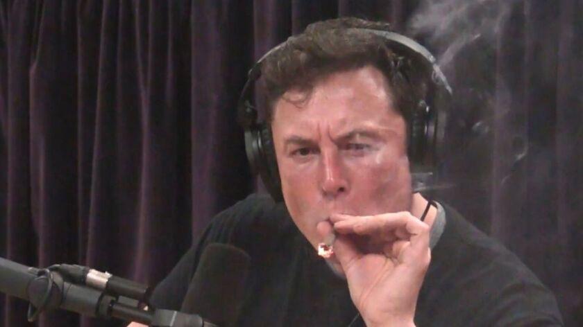 Tesla CEO Elon Musk smokes while next to a microphone.