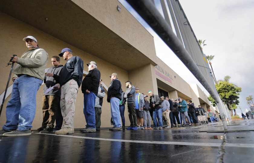 People line up to enter a Crossroads West Gun Show in 2018 at the Del Mar Fairgrounds.