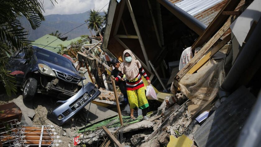 A woman makes her way through the rubble of homes in the Balaroa neighborhood of Palu in Central Sulawesi, Indonesia, on Oct. 2, 2018.