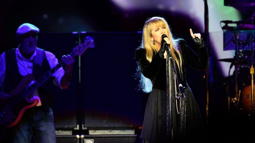 Stevie Nicks performs with Fleetwood Mac in 2013. John McVie is on the right.
