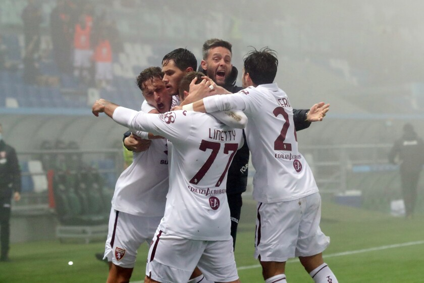 Torino's Mergim Vojvoda and Karol Linetty celebrate a goal with the team during the Serie A soccer match between Sassuolo and Torino, at the Mapei Stadium in Reggio Emilia, Italy, Friday, Oct. 23, 2020. (Fabrizio Zani/LaPresse via AP)