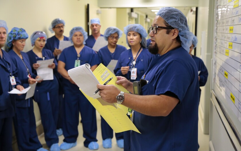 Sam Minero, manager of surgical care at Sharp Memorial Hospital and a registered nurse, talks with surgical nurses and technicians during a daily safety huddle with surgical staff before they begin their day in the different operating rooms.