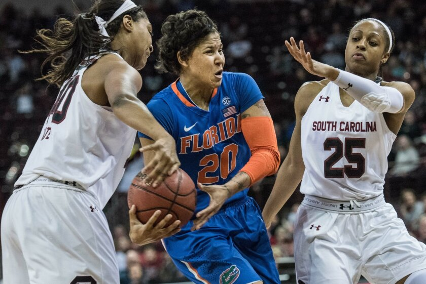Florida guard Simone Westbrook (20) drives to the hoop defended by South Carolina forward Jatarie White, left, and South Carolina guard Tiffany Mitchell (25) during the first half of an NCAA college basketball game Thursday, Feb. 11, 2016, in Columbia, S.C. (AP Photo/Sean Rayford)
