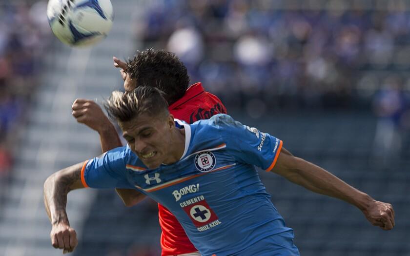 Richard Ruiz, de Cruz Azul, pelea un balón con José Olvera, del Morelia.