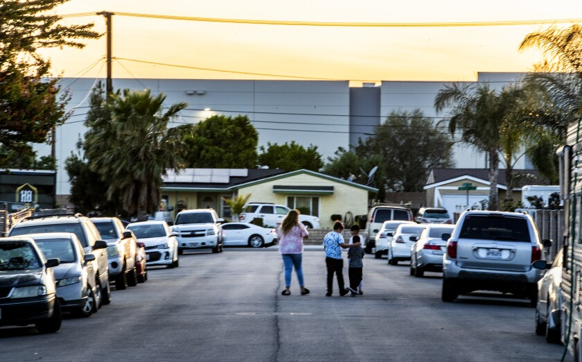 A woman and three children in the middle of a residential street with a warehouse building in the background