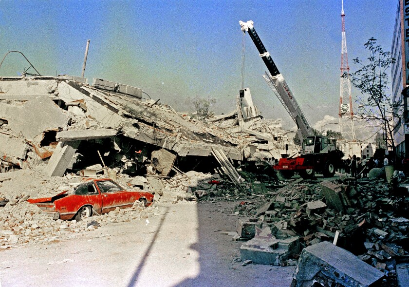 A car sits under rubble after the 1985 Mexico City earthquake