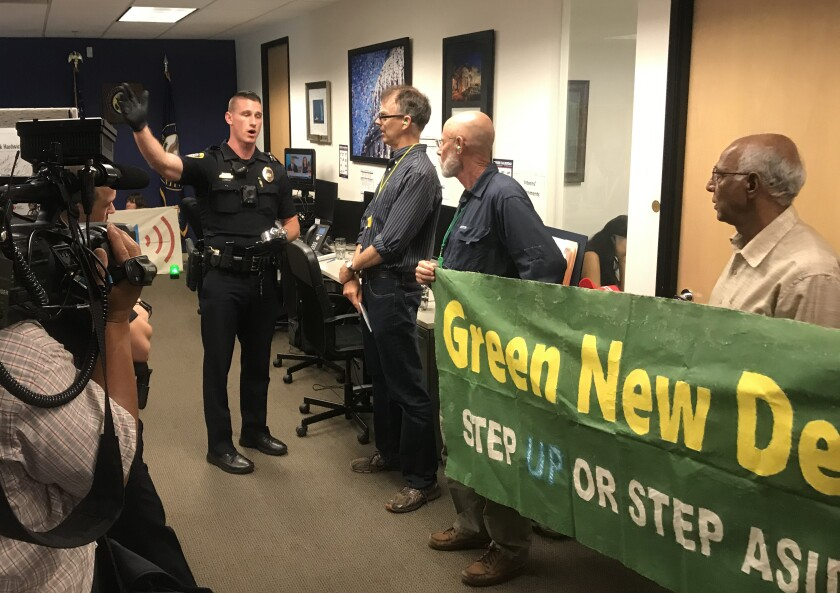 Activists protested outside Rep. Scott Peters office in University City urging him to sign onto the Green New Deal on July 19, 2019. During a more recent protest on Sept. 26, protesters barged into his office.
