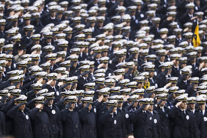 Naval Academy midshipmen salute ahead of a game against Army in Philadelphia on Saturday.