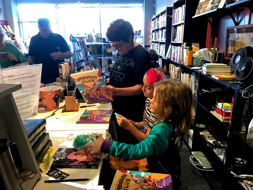A woman in a bookstore helps two children with their books.