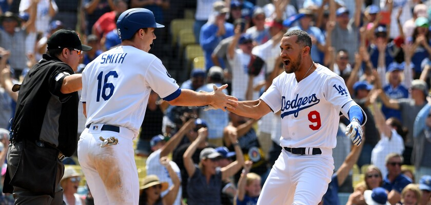 Will Smith congratulates Dodgers teammate Kristopher Negron after he scored the wining run on Aug. 7, 2019.