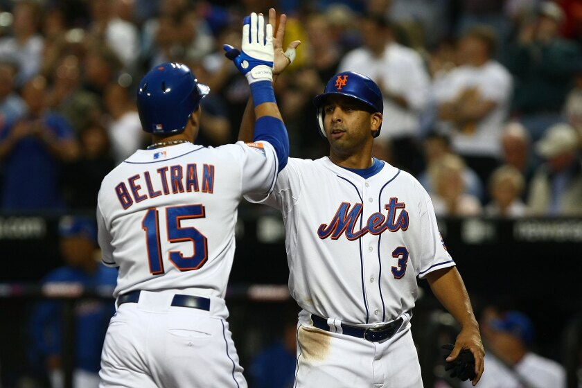Alex Cora congratulates New York Mets teammate Carlos Beltran, who hit a home run against the Philadelphia Phillies during a 2009 game. The two Puerto Rico natives are among those at the center of the Houston Astros sign-stealing scandal.