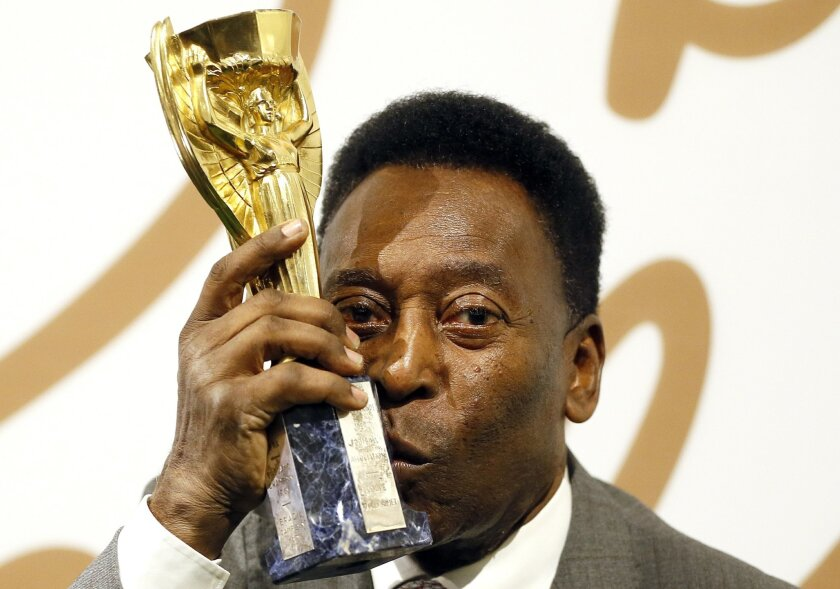 Brazilian former footballer Pele holds up his copy of the Jules Rimet Trophy, during a media opportunity in London, Wednesday, June 1, 2016. The three-time World Cup Champion, FIFA Player of the Century and Brazilian Football icon, will offer his vast collection of memorabilia, awards, personal pro
