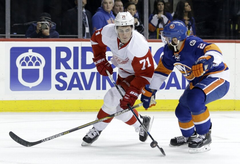 Detroit Red Wings' Dylan Larkin, left, and New York Islanders' Nick Leddy fight for the puck during the first period of an NHL hockey game, Monday, Feb. 15, 2016, in New York. (AP Photo/Seth Wenig)