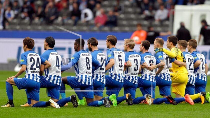 Players of Berlin kneel down prior to the German Bundesliga soccer match between Hertha BSC Berlin a
