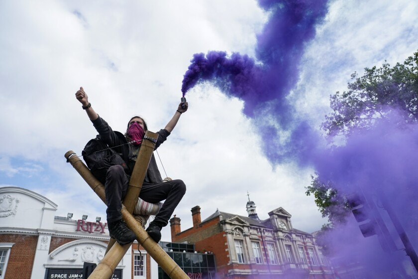 A demonstrator holds a flare in Windrush Square during the annual Afrikan Emancipation Day Reparations march in London, Sunday, Aug. 1, 2021, Black people whose right to live in the U.K. was illegally challenged by the government marked the anniversary Sunday of the act that freed slaves throughout the British Empire, drawing a direct link between slavery and the discrimination they suffered. Dozens of campaigners gathered in Brixton, a center of the Black community in south London, to back the international drive for reparations for the descendants of enslaved Africans and demand legislation to compensate legal residents who were threatened with deportation in what is known as the Windrush Scandal. (AP Photo/Alberto Pezzali)