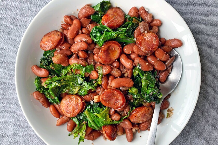A pot of red beans, spiced with andouille sausage, makes a great base for stirring in mustard greens, or any produce box greens you need to use up, for a comforting one-pan dish.