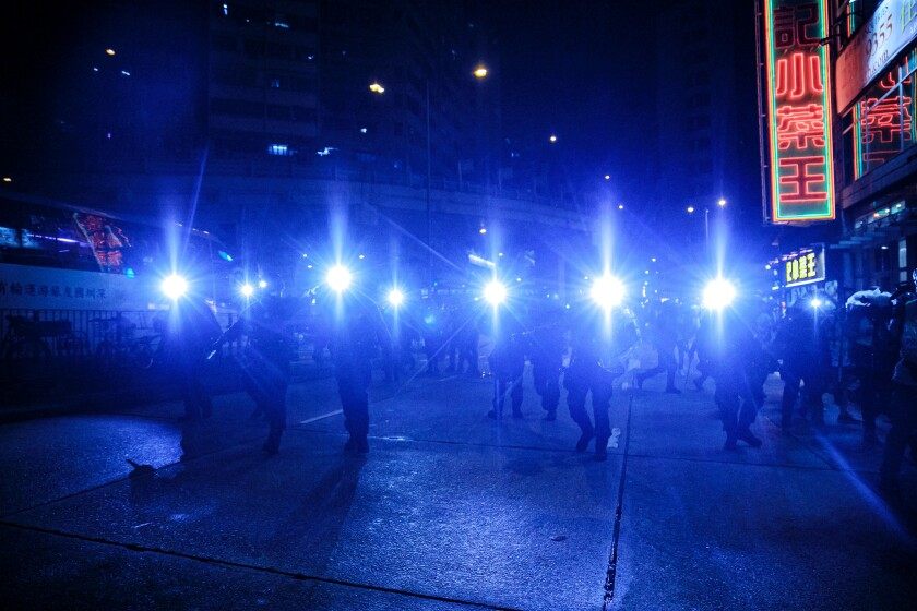 Hong Kong elite police officers chase protesters after they tried to cause a disturbance near the Mongkok Police Station in Hong Kong in 2019.