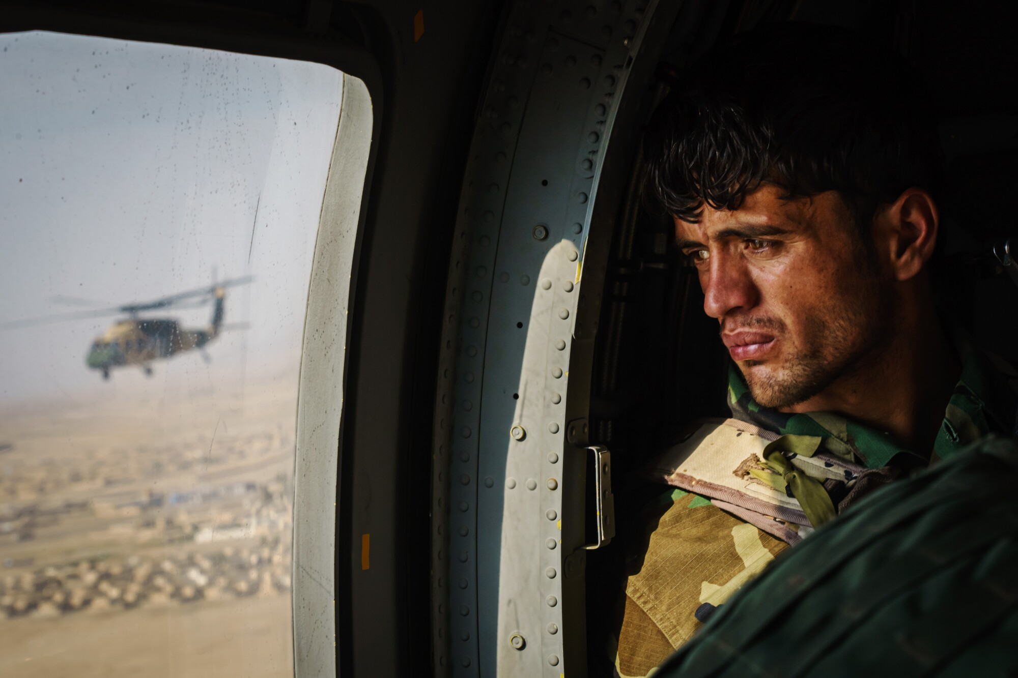 A soldier surveys the terrain out the window during a resupply flight on a UH-60 Black Hawk