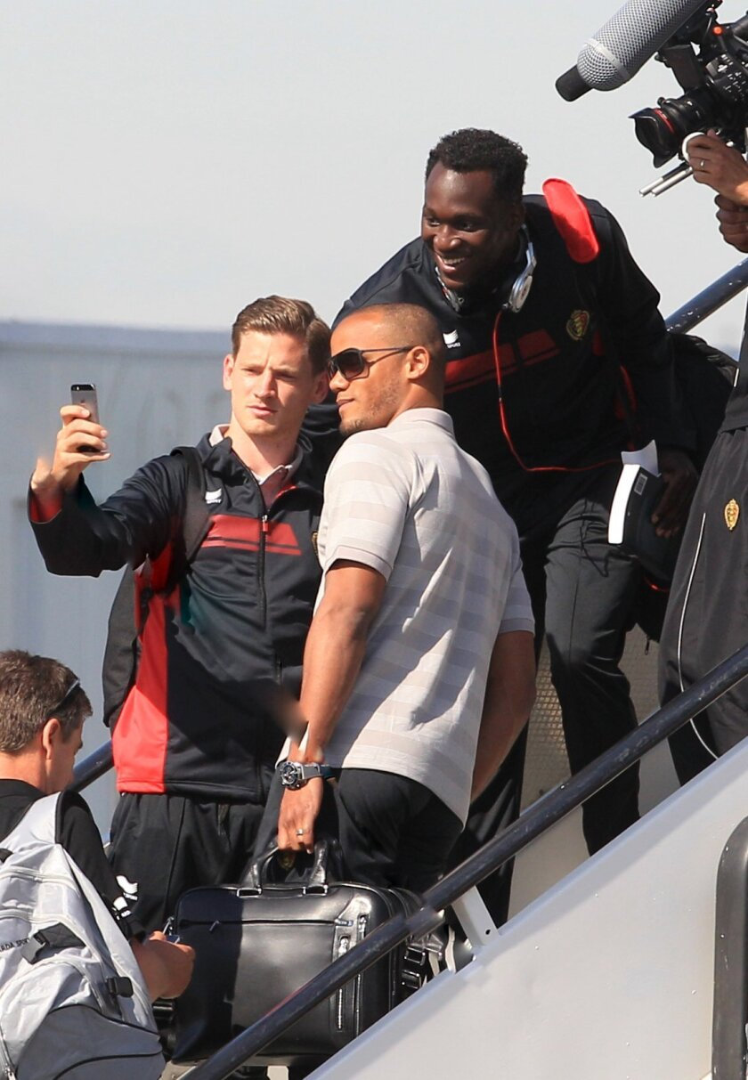 Belgian soccer players Vincent Kompany, center, Romelu Lukaku, top right, and Jan Vertonghen pose for a selfie prior to embarking the plane, departing from Brussels airport to Sao Paulo Brazil, in Brussels, Tuesday, June 10, 2014. Belgium will play against South Korea, Russia and Algeria in Group H of the World Cup 2014 in Brazil. (AP Photo/Yves Logghe)