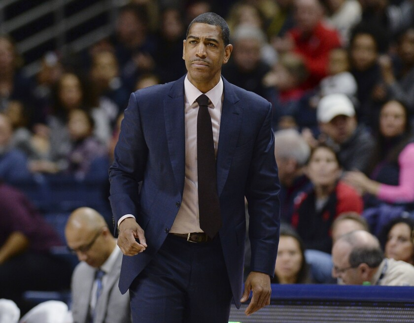 FILE - In this Feb. 25, 2018, file photo, then-Connecticut coach Kevin Ollie watches during the first half the team's NCAA college basketball game in Storrs, Conn. Former Connecticut head coach Kevin Ollie has been brought on board in a leadership role for a new basketball league designed to offer elite high school players another pathway to the pros. Ollie will serve as coach and director of player development for Overtime Elite, which markets itself to 16-to-18 year old players with guarantees of academic education and a six-figure salary. (AP Photo/Jessica Hill, File)