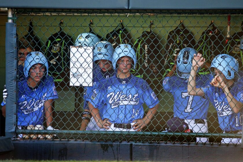 Sweetwater Valley players in the dugout wear their rally helmets during the sixth inning against Pearland (Texas) West on Sunday at the Little League World Series. Pearland won 8-4. (AP Photo/Gene J. Puskar)