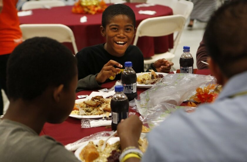 Jaisean Woodso, 9, smiles as he enjoys a turkey dinner at the Union Rescue Mission in Los Angeles last fall. Charitable giving may have reached a new record in 2013, a group estimates.