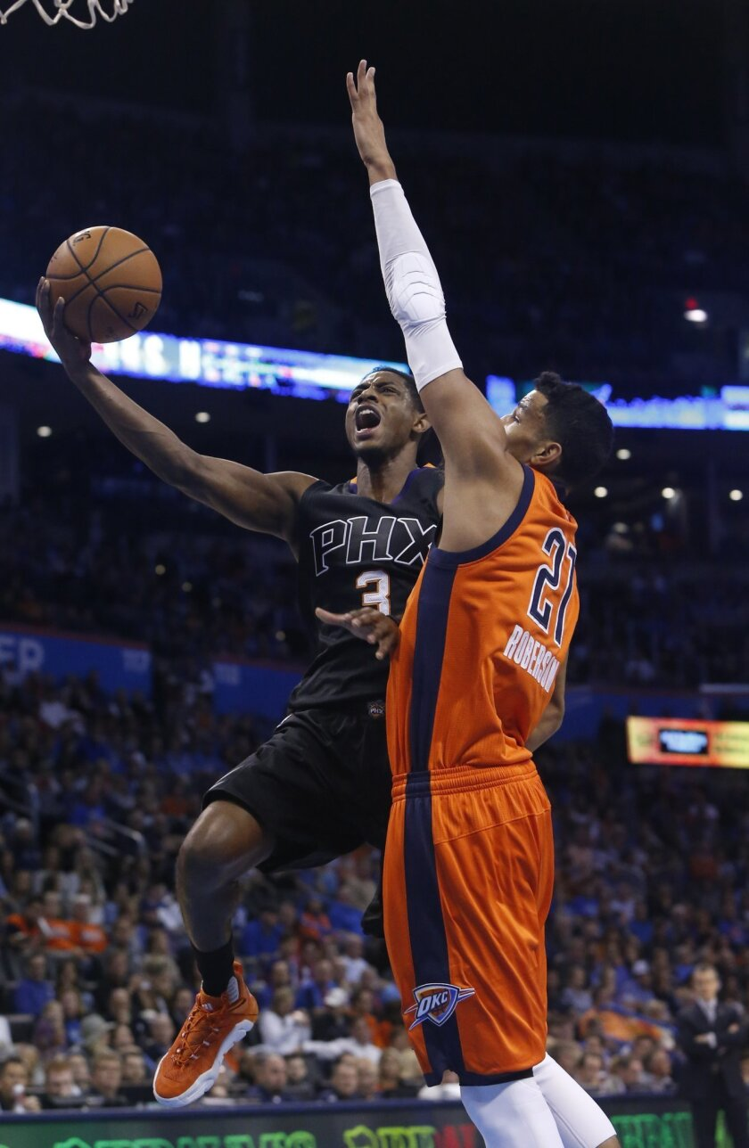 Phoenix Suns guard Brandon Knight (3) shoots as Oklahoma City Thunder guard Andre Roberson (21) defends in the first quarter of an NBA basketball game in Oklahoma City, Sunday, Nov. 8, 2015. (AP Photo/Sue Ogrocki)
