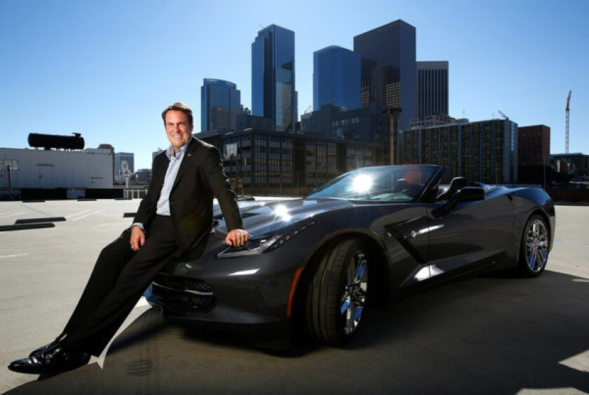 Mark Reuss, President of General Motors, is photographed in downtown Los Angeles next to the company's new 2014 Corvette Stingray convertible. Reuss hinted that a version of the Corvette could be a hybrid.