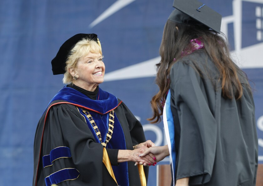 Retiring Can State San Marcos President Karen Haynes congratulates a student at a 2019 graduation in San Marcos.