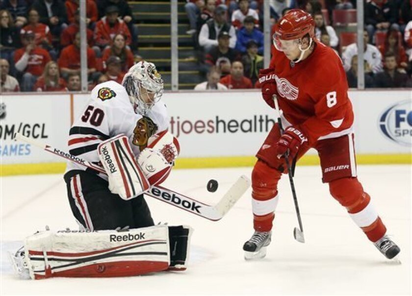 Chicago Blackhawks goalie Corey Crawford (50) makes a save on a shot by Detroit Red Wings left wing Justin Abdelkader (8) in the second period of an NHL hockey game Sunday, March 31, 2013, in Detroit. (AP Photo/Duane Burleson)