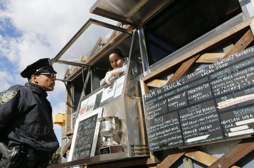 """Snowday staffer Marivette Alicea, 25, right, discusses the food truck's """"gourmet lumberjack"""" menu with a New York city police officer as he decides what to order during Smorgasburg at Brooklyn's Grand Army Plaza, Sunday, Oct. 18, 2015, in New York. The truck is part of the nonprofit Drive Train pro"""