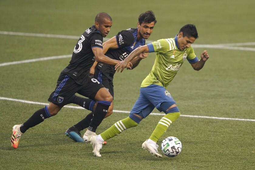 El delantero peruano Raúl Ruidíaz, derecha, de los Sounders de Seattle, avanza con el balón