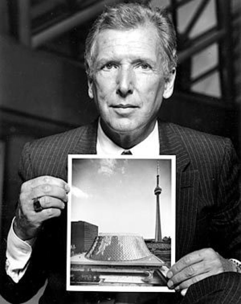 Arthur Erickson, shown in 1982, displays a photo of Roy Thompson Hall in Toronto, which he helped design. Erickson first achieved international notice when he and a colleague won a contest to design the campus of Simon Fraser University.