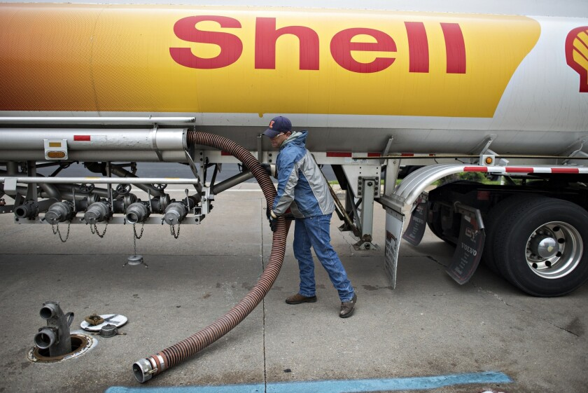 Travis Simmons, a driver for Yo-Mac Transport, stores a filling hose after delivering gasoline to a Shell station in Peoria, Ill., on Friday. Nationwide, the price for regular gasoline fell to $3.395 a gallon Saturday, the lowest since February, according to AAA.