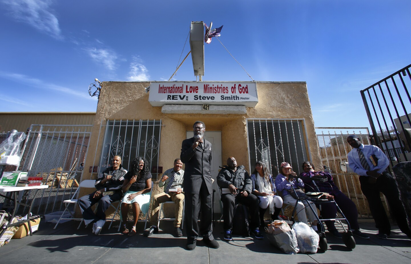 Standing in front of their former church building, the International Love Ministries of God on 16th Street in downtown San Diego, Rev. Steve Smith preaches on Sunday morning to his congregation. The group loss their lease at the end of December but continue to meet out in front on the city sidewalk.