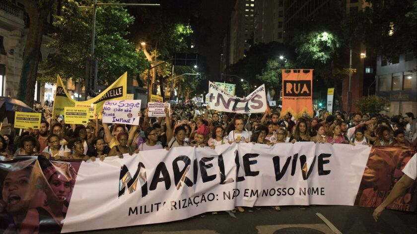 "People hold a banner that reads in Portuguese ""Marielle lives"" during a protest against the murder o"