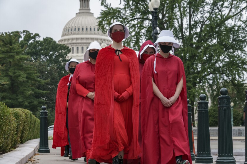 """Activists dressed as characters from """"The Handmaid's Tale"""" protest Sunday on Capitol Hill in Washington, D.C."""