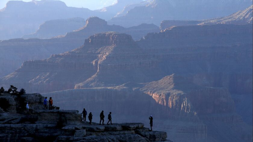GRAND CANYON, AZ., MARCH 9, 2015: Visitors to one of the viewing spots at Mather Point venture beyon