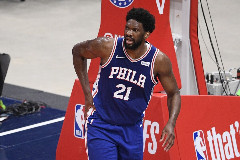 Philadelphia 76ers center Joel Embiid (21) touches his right side after he fell on the court during the first half of Game 4 in a first-round NBA basketball playoff series against the Washington Wizards, Monday, May 31, 2021, in Washington. (AP Photo/Nick Wass)