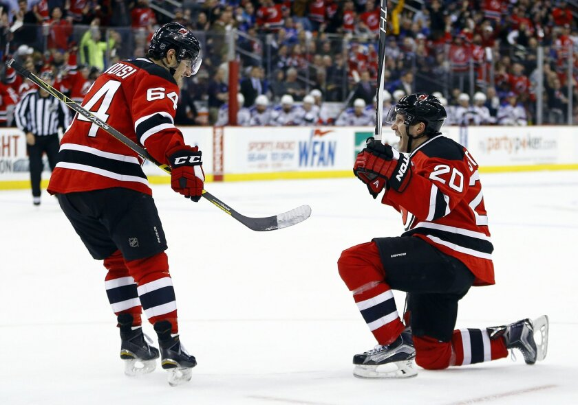 New Jersey Devils right wing Lee Stempniak (20) and center Joseph Blandisi (64) celebrate a goal by Stempniak's goal against the New York Rangers during the second period of an NHL hockey game, Tuesday, Feb. 23, 2016, in Newark, N.J. (AP Photo/Julio Cortez)