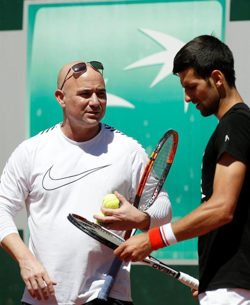 Novak Djokovic (R) of Serbia talks with his new coach Andre Agassi (L) of the USA during a training session few days ahead of the French Open tennis tournament at Roland Garros in Paris, France, 25 May 2017 (reissued 31 March 2018). EFE