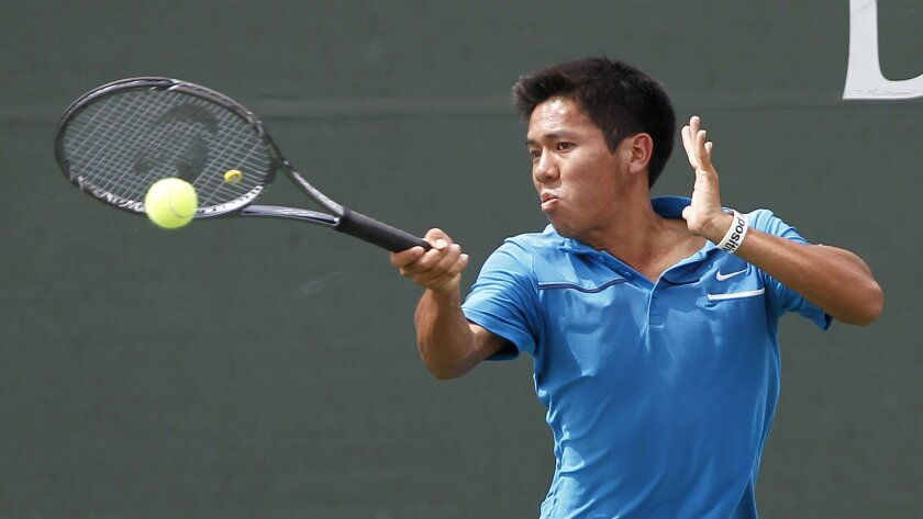On a windy day at the Barnes Tennis Center, Rancho Bernardo senior Tyler Pham returns a shot en route to his second straight San Diego Section singles championship.