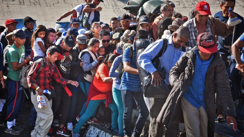 Central American migrants with children, backpacks, sleeping rolls and food crowd a makeshift footbridge over the sewage polluted Tijuana River. After a torturous 2,000 mile journey many mistakenly believed they could surge as a group and cross into the United States.