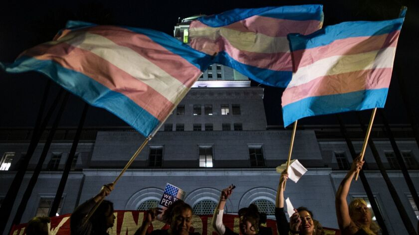 Flags are waved as people gather on the steps of Los Angeles City Hall for a rally in support of transgender rights on Oct. 22.