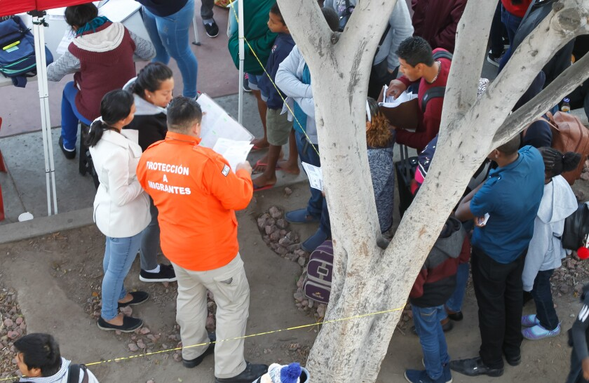 An official with Grupo Beta (orange jacket) checks identification documents against the list in a notebook of asylum seekers as he prepares a group to be taken to the U.S. border for processing.