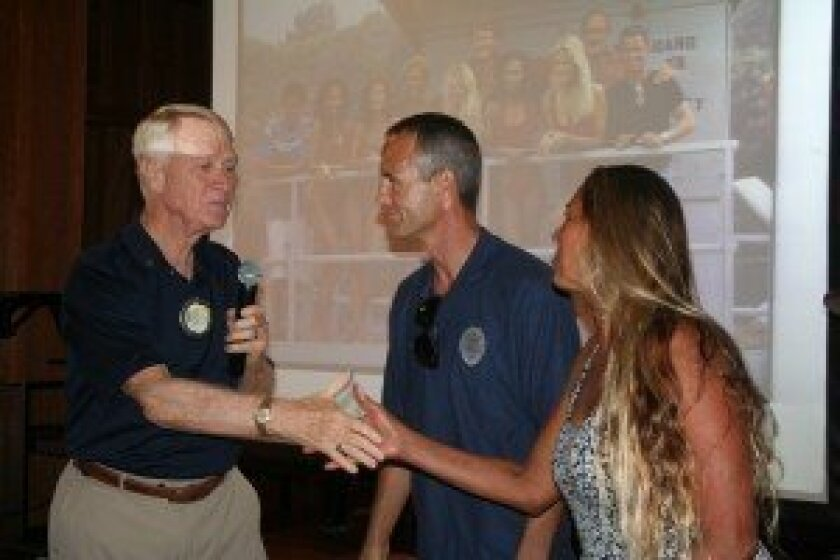Rotarian Marty Peters presents Lt. Jon Edelbrock and Liza Rogers with a $500 check. Photo by Kristina Houck