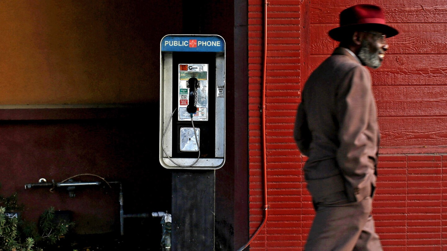 A man walks past a pay phone on South Leimert Boulevard in Los Angeles. Of California's 27,000 pay phones, most are concentrated in L.A. County, the San Francisco Bay Area and along the Interstate 5 corridor, according to the Public Utilities Commission.